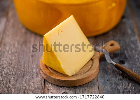 Medium hard cheese head edam gouda parmesan on wooden board with knife wooden texture daylight side view