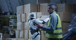 Medium long shot of a man using a tablet while watching a robot working in a warehouse