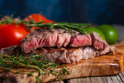 Medium rare grilled beef steak ribeye with rosemary and tomatoes on wooden cutting board on dark blue background. Appetizing image for restaurant menu. Delicious food. Juicy meat.