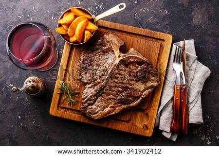 Medium rare Grilled T-Bone Steak with potato wedges and wine on serving board block on dark background