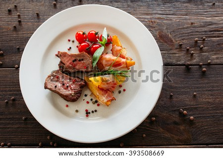 Medium rare pork steak with fresh vegetables. Food fotography of pork steak with potatoes and tomatoes cherry. Tasty cook meat with vegetables on dark wooden background.