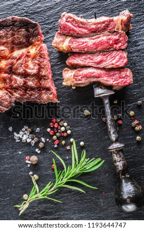 Medium rare Ribeye steak or beef steak on graphite background. Top view.