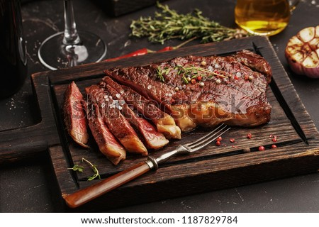 Medium rare sliced grilled striploin beef steak served on wooden board with vintage fork, glass of wine, herbs and spices