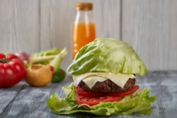 medium roast beef hamburger with salad, without buns on a wooden background, accompanied by fresh vegetables and juice