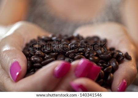 Medium  Roasted Coffee beans in woman's hands