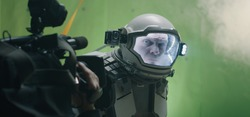 Medium shot of a cameraman filming a sci-fi scene with a astronaut looking around