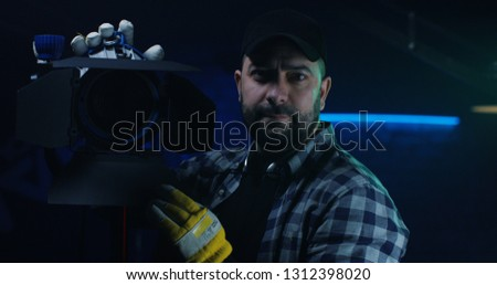 Medium shot of a cameraman holding a Fresnel lamp while looking at the camera #1312398020