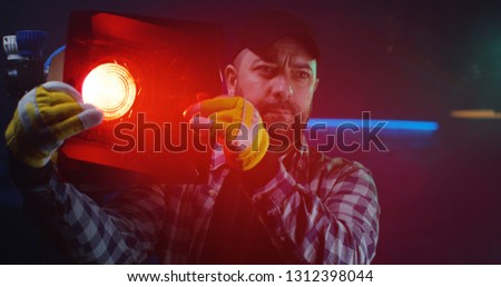 Medium shot of a cameraman testing a Fresnel lamp with red lighting gel #1312398044