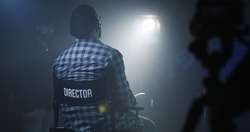 Medium shot of a director sitting in his chair on a film set