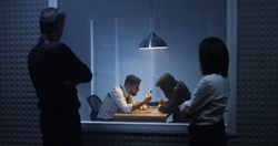 Medium shot of a male and a female investigator watching their colleague interrogating a drug dealer