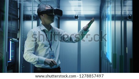Medium shot of a male technician in VR glasses using two virtual interfaces while working in a data center #1278857497