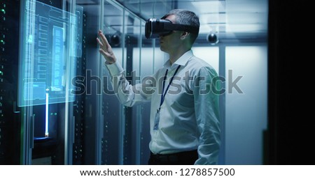 Medium shot of a male technician in VR glasses using two virtual interfaces while working in a data center #1278857500