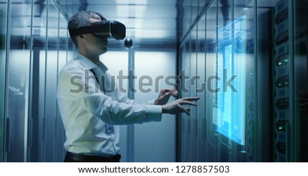 Medium shot of a male technician in VR glasses using two virtual interfaces while working in a data center #1278857503