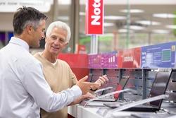 Medium shot of a salesman showing laptops to an elderly man in an electronics store.