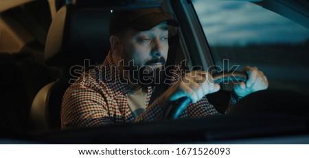 Photo of  Medium shot of a sleepy man slapping himself while driving his car at night