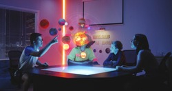 Medium shot of a teacher and her students looking at a solar system hologram in an astronomy class