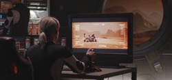 Medium shot of a young woman controlling Mars rover with a remote controller in a base