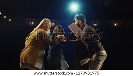 Medium shot of actors and actresses throwing scripts away and hugging while celebrating on stage in a theater