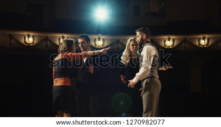 Medium shot of actors rehearsing in a theater while reading their scripts #1270982077