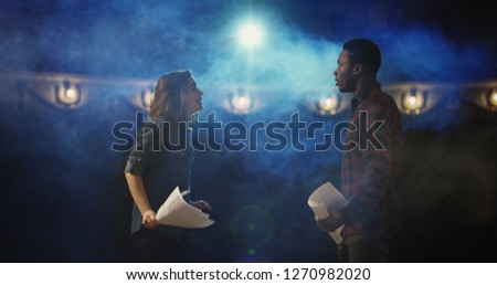 Medium shot of an actor and actress rehearsing a scene in the theater while holding their scripts
