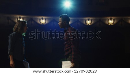 Medium shot of an actor and actress rehearsing a scene in the theater while holding their scripts #1270982029