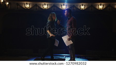 Medium shot of an actor and actress rehearsing a scene in the theater while holding their scripts #1270982032