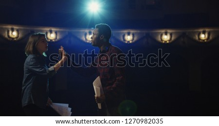 Medium shot of an actor and actress rehearsing a scene in the theater while holding their scripts #1270982035