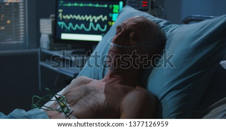 Medium shot of an elderly male patient sleeping and a heart monitor showing vital signs