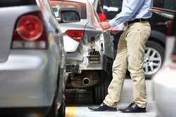 Medium shot of an insurance assessor making notes on a clipboard while inspecting a damaged vehicle at a garage.