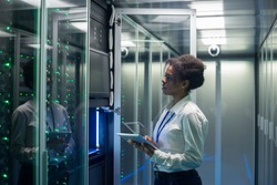 Medium shot of female technician working on a tablet in a data center full of rack servers running diagnostics and maintenance on the system