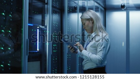 Medium shot of female technician working on a tablet in a data center full of rack servers running diagnostics and maintenance on the system #1215128155