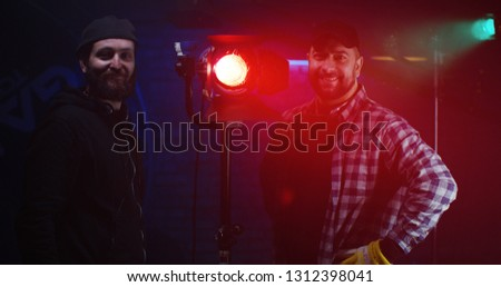 Medium shot of film crew looking at camera while using a Fresnel lamp #1312398041