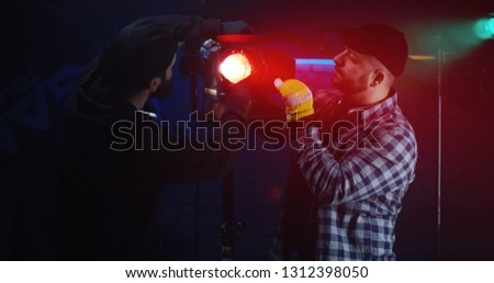 Medium shot of film crew looking at camera while using a Fresnel lamp #1312398050