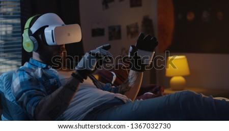 Medium shot of man lying in bed using virtual reality headset and exoskeleton gloves
