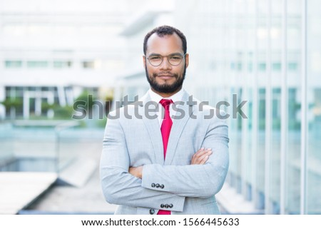 Medium shot of smiling bearded businessman. Handsome confident young man with crossed arms looking at camera. Concept of confidence