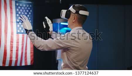 Medium shot of technician using VR headset and exoskeleton gloves