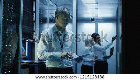 Medium shot of technicians working on a laptop in a data center full of rack servers running diagnostics and maintenance on the system