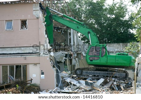 Medium weight shovel tearing down a building in preparation for construction.