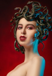medusa gorgon with bare shoulders looking at camera on red background