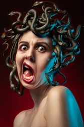 medusa gorgon with bare shoulders looking at camera on red background, screaming