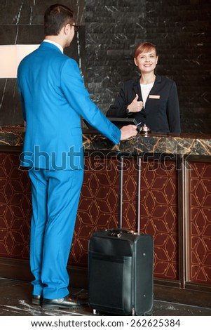Meeting a guest. Full length selective focus view of the charming female receptionist showing her thumb up and meeting a guest businessman in blue suit with the suitcase below