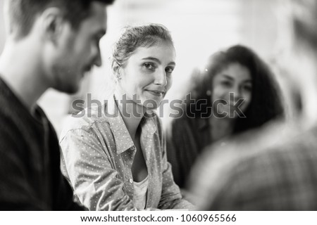 Meeting at the startup office . A working multiethnic group meets to study a new project. Focus on a young beautiful woman looking at camera. Black and white picture