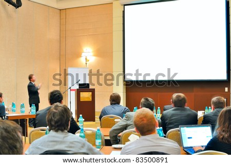 meeting, conference, presentation in auditorium with blank screen - stock photo