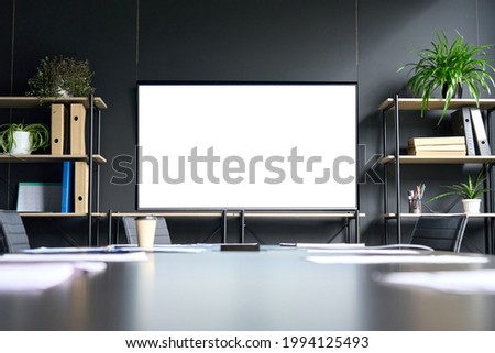 Meeting conference room with blank empty mockup tv screen monitor for advertising standing in modern contemporary office on black wall background. No people. Business technologies concept. Stockfoto ©