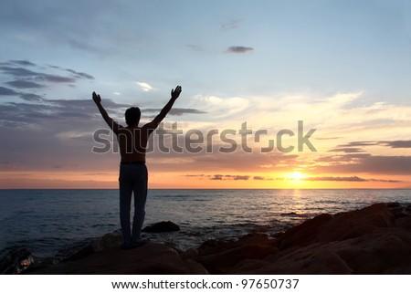 Meeting dawn on  sea.  silhouette of  man.
