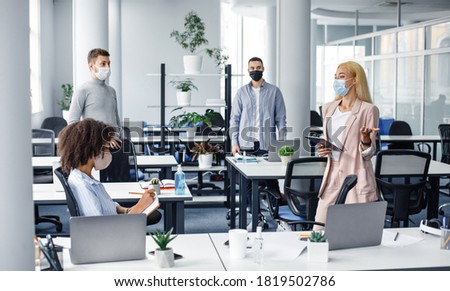 Meeting in office and instructions from boss during social distancing and virus outbreak. Young business woman in protective mask in suit with tablet in hand speaks to workers at workplace