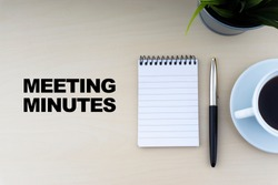 MEETING MINUTES text with fountain pen, notepad, and decorative flower on wooden background. Business and copy space concept.