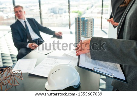 Meeting of architects and business investors, model of modern multi storey residential building house plans and hardhat on table , construction planning concept