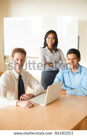 Meeting of diverse team of business people in bright conference room, Asian female, Latino man and Caucasian male sitting around table with laptop smiling, looking at camera. Vertical copy space