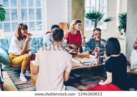 Meeting of hipster friends dressed in casual wear in modern apartment on weekend.Young people spending leisure time together have party at home with pizza and alkohol